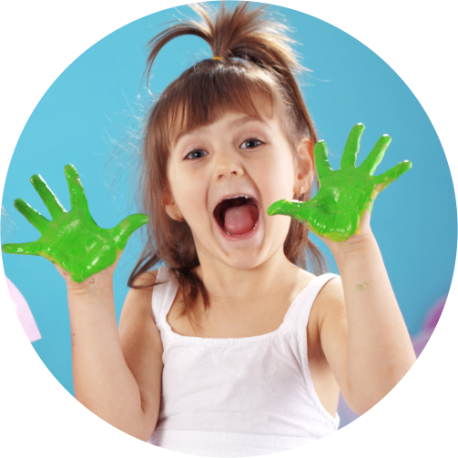A cute young girl showing her palms with green paint on it